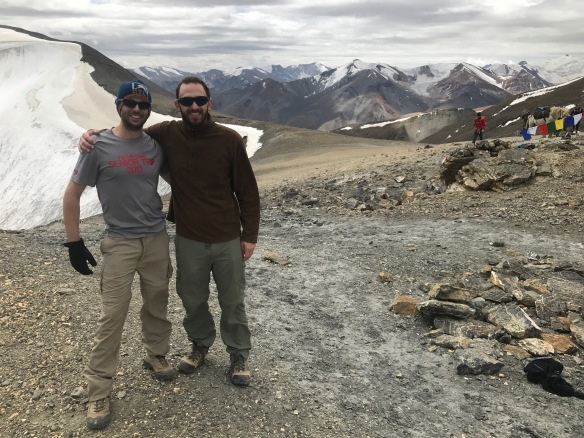 Dr Daniel Baker and Dr Zac Hardy are shown standing together in Phirste La Pass by a snow-tipped mountain peak.
