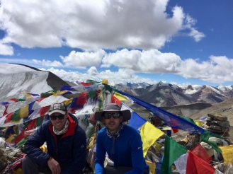 Dr Mark Kushinka and Dr Rob Razick are sitting at camp in Phirste La Pass at 18,208 ft. The camp is designated by banners of alternating color flags attached to the top of a pole and pinned to the ground. Mountains are shown around them with blue sky.